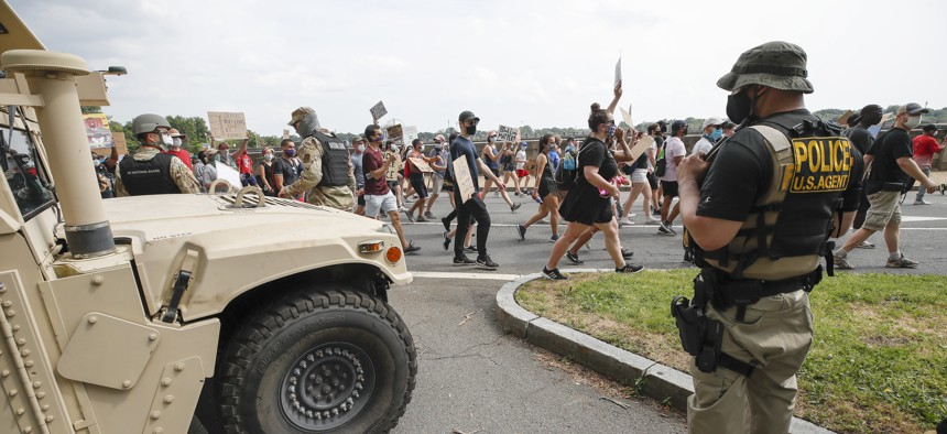 DC National Guard soldiers and other law enforcement personnel watch as demonstrators protest Saturday, June 6, 2020, along Independence Avenue in Washington, over the death of George Floyd, a black man who was in police custody in Minneapolis.