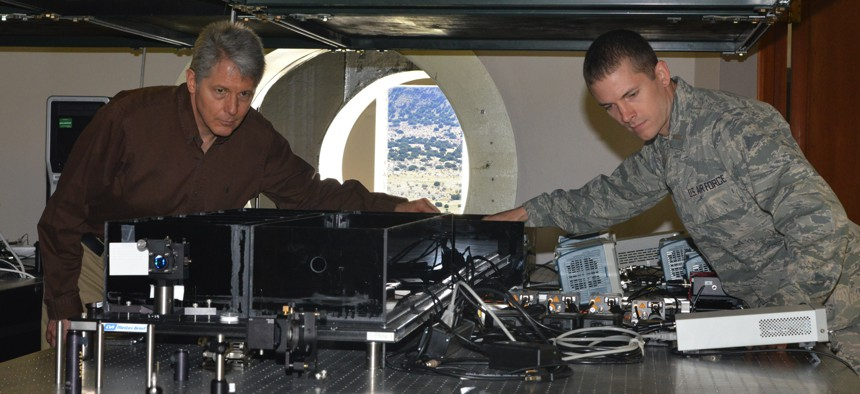 Air Force Research Laboratory researchers Mark Gruneisen and 2nd Lt. Eddie Hilburn make adjustments to the quantum key distribution testbed at the Starfire Optical range propagation site in 2019.
