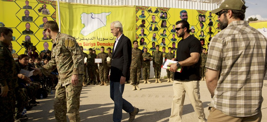 U.S. envoy William Roebuck, center, leaves the podium after speaking at a ceremony to celebrate U.S.-backed Syrian Democratic Forces (SDF) defeat of Islamic State militants in Baghouz, at al-Omar Oil Field base, Syria, Saturday, March 23, 2019.