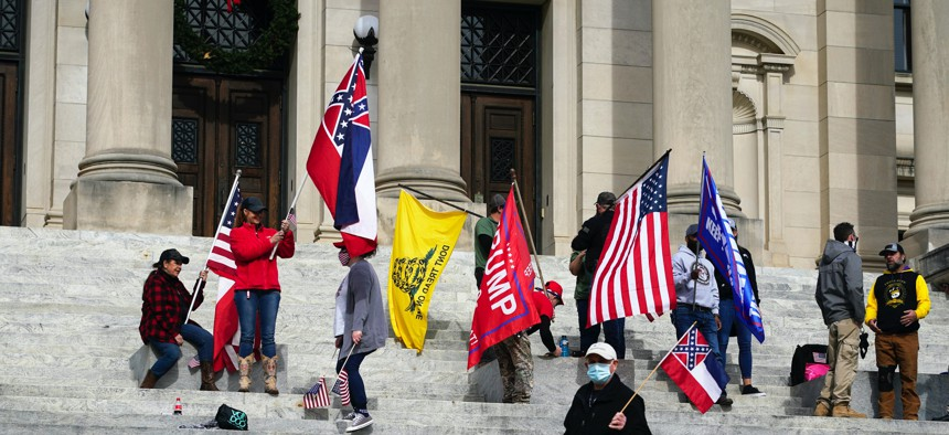 Protestors at the Mississippi state capitol wave the former state flag with its Confederate emblem, the Gadsden flag, and pro-Trump banners on Jan. 6, 2021.