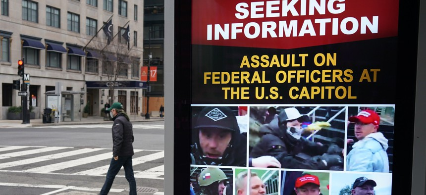 A monitor at a bus shelter near the White House shows images of people wanted in connection with the insurrection at the US Capitol in Washington, DC on January 14, 2021.
