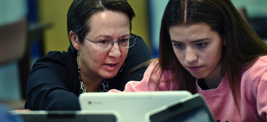 A teacher librarian at Brookfield, Conn., High School works with a freshman in her Digital Student class, a required course in which students learn to evaluate online information.
