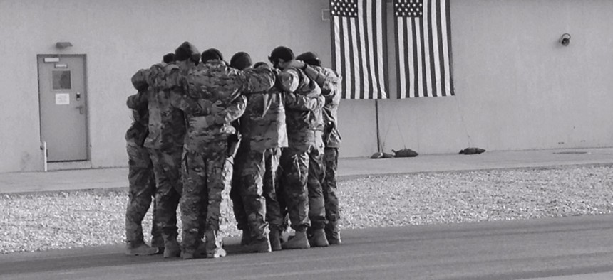 Soldiers of Special Forces, 10th Special Forces Group (Airborne) huddle together for strength as they memorialize two of their fallen brothers during a memorial held at Kunduz Airfield in Afghanistan on Nov. 7, 2016.
