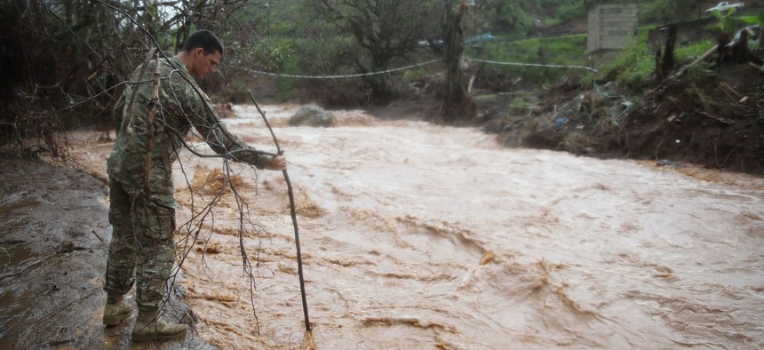 U.S. Army 1st Special Force Command Staff Sgt. Eric Reyes checks the depth of a river that was caused when heavy rains fell on the area days after Hurricane Maria swept through the island on October 7, 2017 in Barranquitas, Puerto Rico.