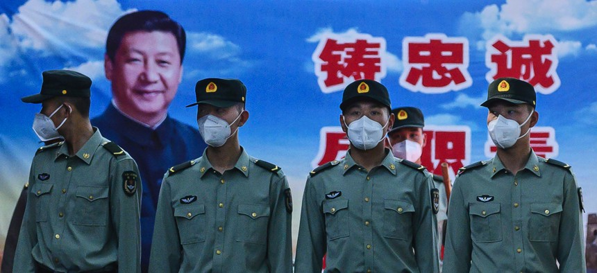 Soldiers of the People's Liberation Army's Honour Guard Battalion wear protective masks as they stand at attention in front of photo of China's president Xi Jinping at their barracks outside the Forbidden City, near Tiananmen Square