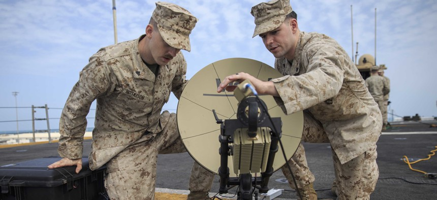 U.S. Marine Corporals Josrdan Hoskison, left, and Jacob Jusczak, right, both data system administrators with the 22nd Marine Expeditionary Unit, set up a Multi-Mission Terminal satellite on the flight deck of the USS Kearsarge.