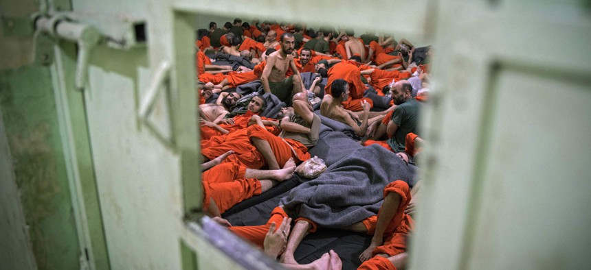 Men, suspected of being affiliated with the Islamic State (IS) group, gather in a prison cell in the northeastern Syrian city of Hasakeh on October 26, 2019.