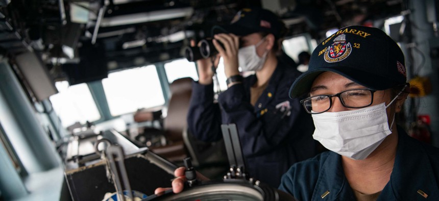 Ens. Jessica Cruz shoots a line of bearing on the bridge of the guided-missile destroyer USS Barry (DDG 62) as the ship conducts routine underway operations in the Taiwan Strait.