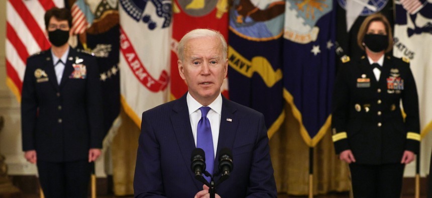 U.S. President Joe Biden delivers remarks on International Women's Day as Air Force General Jacqueline Van Ovost (L) and Army Lieutenant General Laura Richardson (R) listen during an announcement at the East Room of the White House March 8, 2021.