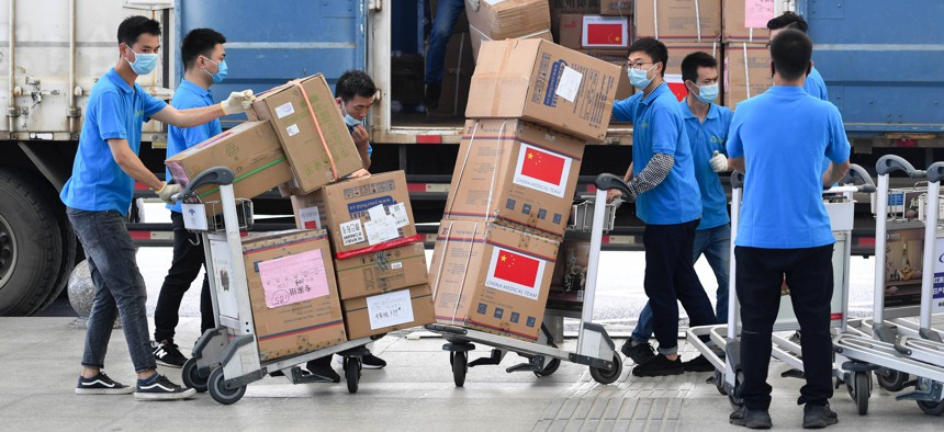 Workers carry boxes of medical supplies which will be donated to Zimbabwe at Huanghua International Airport on May 10, 2020 in Changsha, Hunan Province of China.