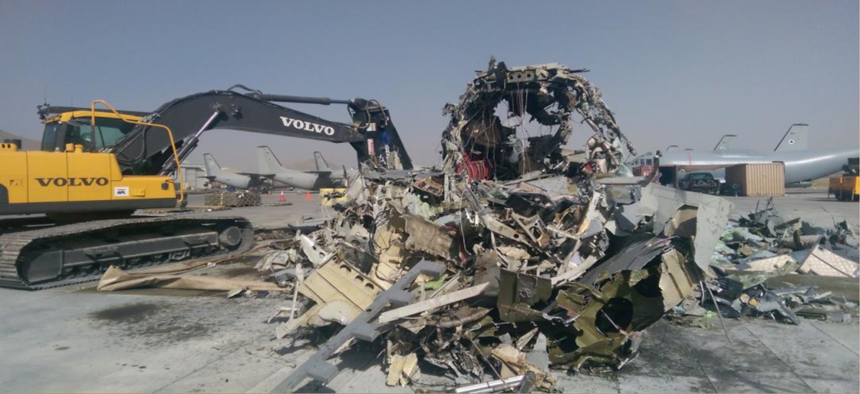 A G.222 aircraft is shredded for scrap at a Kabul airport in August 2014.