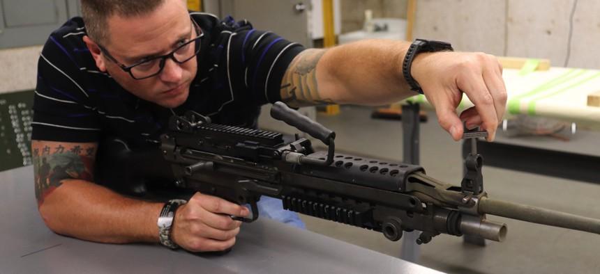 David Blaylock, Simulation & Test Range Division chief, uses a 3D-printed part to adjust an M240 machine gun.