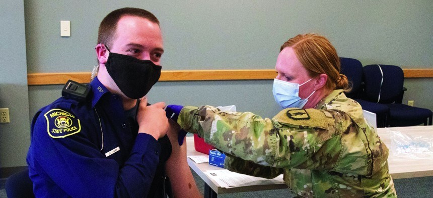 A Michigan Army National Guard medic gives a final dose of the COVID-19 vaccine to a Michigan State Police trooper at police headquarters in Dimondale, Michigan, March 4, 2021.