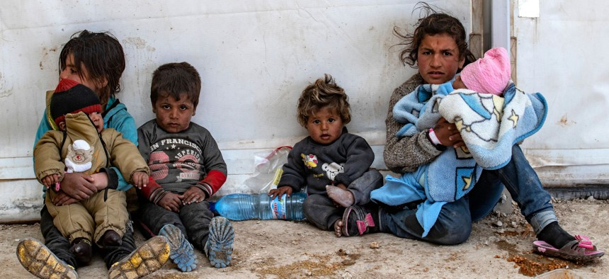 Syrian women and children sit by their belongings to wait for departure from the Kurdish-run al-Hol camp, which holds suspected relatives of ISIS fighters, in Hasakeh governorate of northeastern Syria, on March 18, 2021.