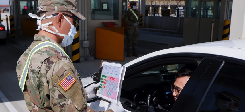 A soldier from the 2nd Armored Brigade Combat Team interviews a driver coming through the Adams Gate at U.S. Army Garrison-Humphreys, South Korea.