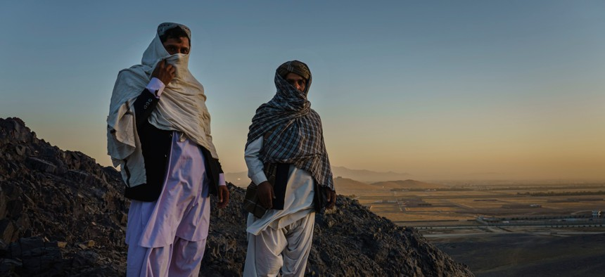 Rohullah Salhe, 35, former Taliban member and former prisoner, left, and Jumah Gul, 40, right, a Taliban commander, stand in the mountains on the outskirts of Kandahar, Afghanistan, on Monday Oct. 26, 2020.