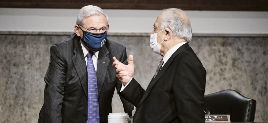 Senate Foreign Relations Committee Chairman Sen. Bob Menendez, D-N.J., left, talks with Zalmay Khalilzad, special envoy for Afghanistan Reconciliation, right, at the end of a hearing on Capitol Hill in Washington, April 27, 2021.