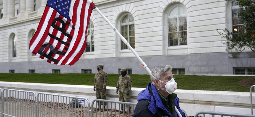 A protester walks past the Russell Senate Office Building on Capitol Hill in Washington, Friday, Jan. 8, 2021.