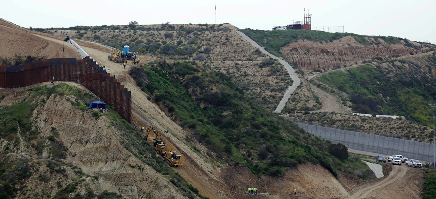 In this March 11, 2019, file photo, construction crews replace a section of the primary wall separating San Diego, above right, and Tijuana, Mexico, below left, seen from Tijuana, Mexico.