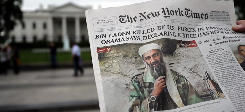 A man reads the front page of a newspaper featuring a picture of Al-Qaeda leader Osama bin Laden, in front of the White House in Washington, DC, on May 2, 2011
