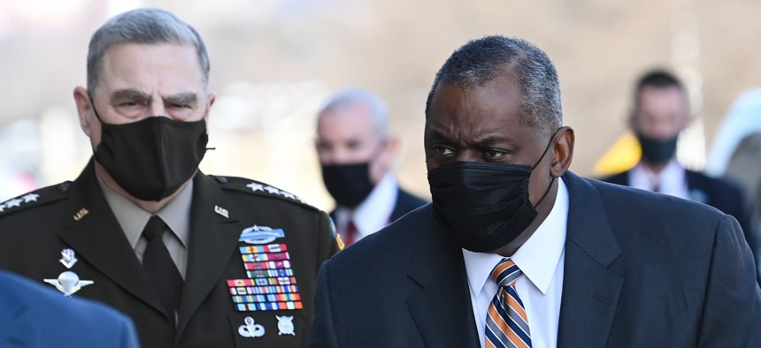 Chairman of the Joint Chiefs of Staff Gen. Mark Milley, left, looks on as Defense Secretary Lloyd Austin arrives at the Pentagon.