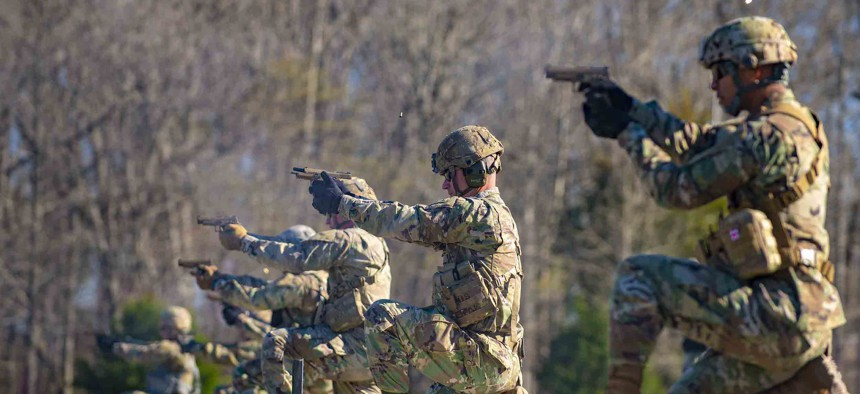 Soldiers fire M17 semi-automatic pistols during the 2021 Fort Knox and First Army Division East Best Warrior Competition at Fort Knox, Ky., March 29, 2021.
