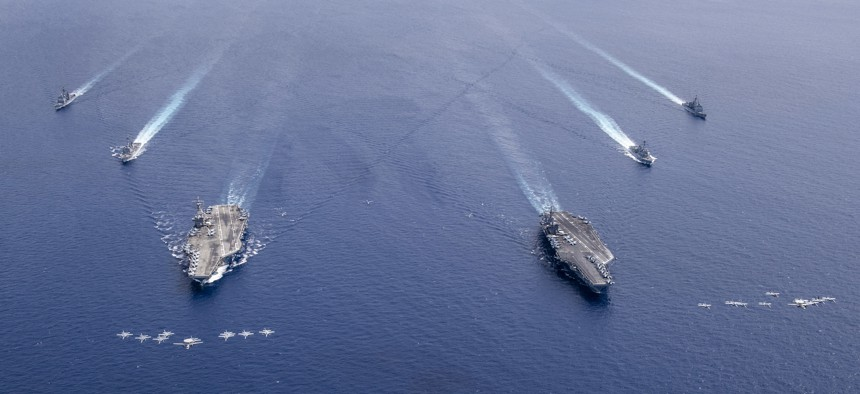 Military aircraft fly in formation over the Nimitz Carrier Strike Force including the aircraft carriers USS Nimitz, right, and USS Ronald Reagan, as they conduct dual carrier operations in the South China Sea, July 6, 2020.