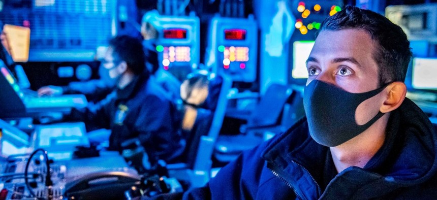 Navy Lt. Louis Petro stands watch as the tactical action officer in the combat information center aboard the USS Germantown in the East China Sea, July 17, 2020.
