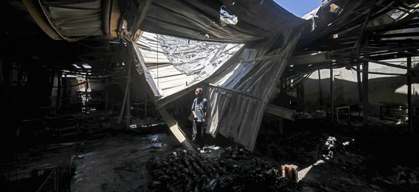 A Palestinian worker salvages items from a damaged factory in Gaza's industrial area, on May 25, 2021.