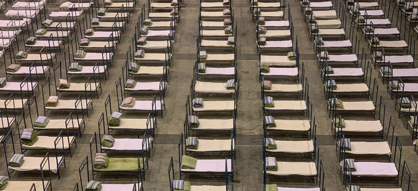 Workers set up beds at an exhibition centre that was converted into a hospital in Wuhan in China's central Hubei province on February 4, 2020.