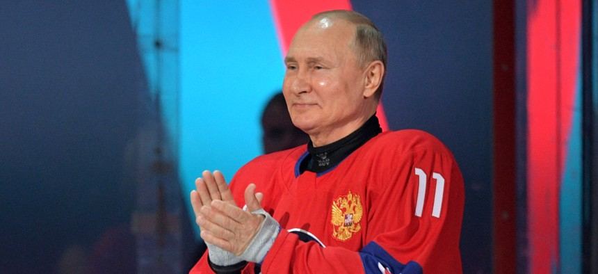 Russian President Vladimir Putin applauds as he attends the opening ceremony of the Night Hockey League gala-match at the Bolshoy Ice Dome in Sochi, on May 10, 2021.