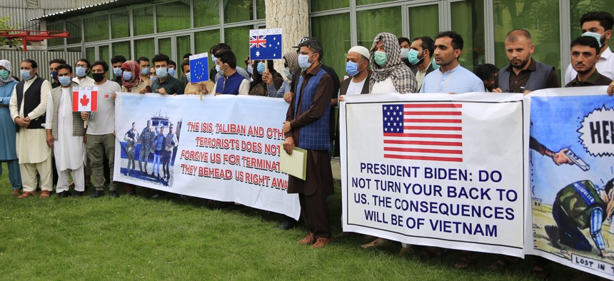 Former Afghan interpreters hold placards during a protest against the U.S. government and NATO in Kabul, Afghanistan, on April 30.