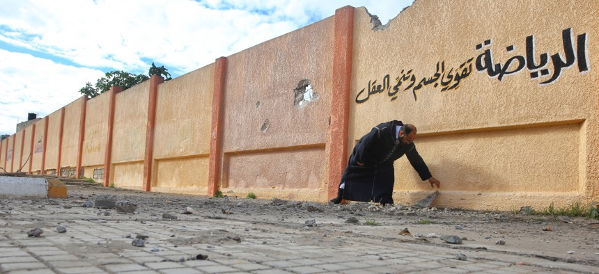 A school director in Tripoli, Libya, shows holes on the wall of a damaged school building that was targeted by airstrikes of Haftars' forces on January 10, 2020.