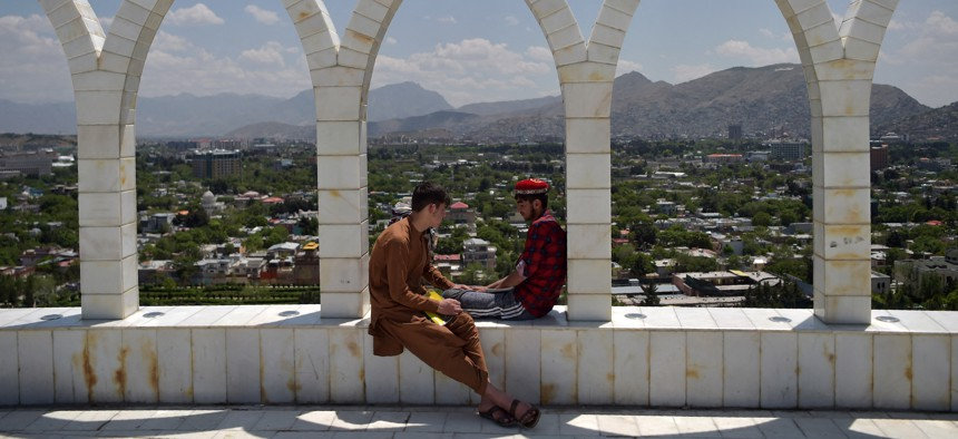 Youths sit at the Wazir Akbar Khan hilltop overlooking Kabul on May 11, 2021.