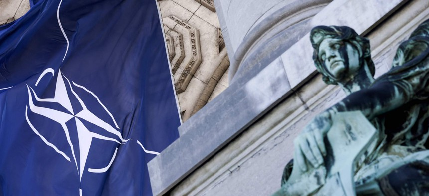 A NATO flag is pictured next to a statue on June 13, 2021, at Parc du Cinquantenaire in Brussels.