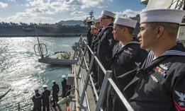 Sailors aboard the Arleigh Burke-class guided-missile destroyer USS Stethem man the rails as the ship enters port in Busan, South Korea, Oct. 21, 2017.
