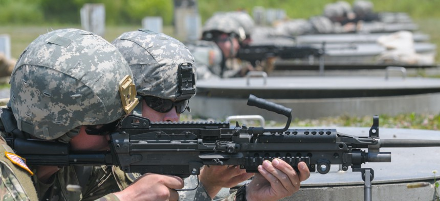 A soldier with the 1229th Transportation Company, Maryland Army National Guard, fires an M249 light machine gun during the unit's annual training at Camp Dawson, West Virginia, on June 11, 2016.