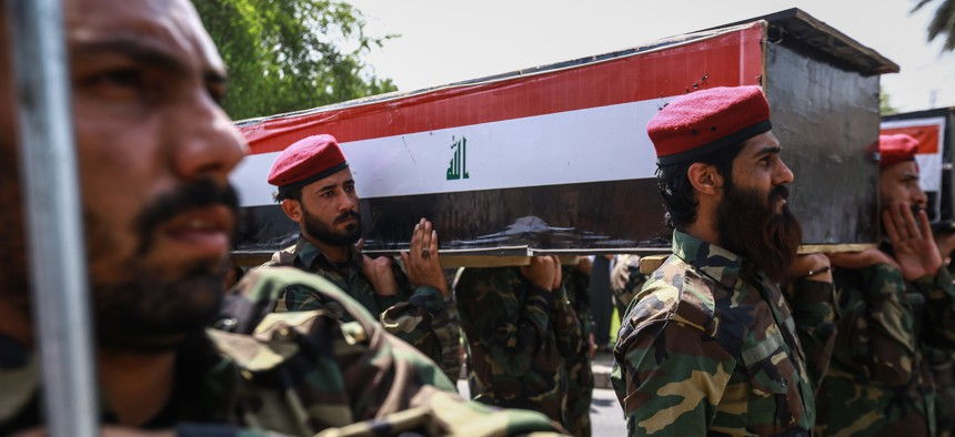 Members of the Popular Mobilization Forces, also known as the Hashd al-Shaabi, carry the body of a colleague, killed along with six others during US airstrikes on the Iraqi-Syrian border city of Al-Qaim on June 29, 2021.