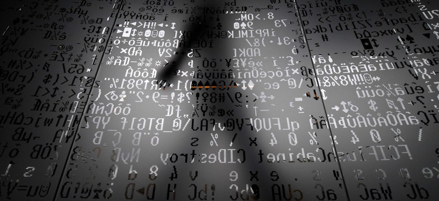 A picture taken on October 17, 2016 shows an employee walking behind a glass wall with machine coding symbols at the headquarters of Internet security giant Kaspersky in Moscow.