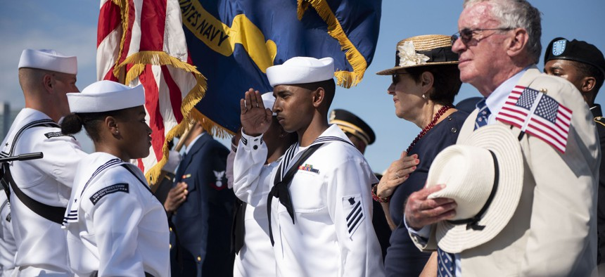 Soldiers, Sailors, Airmen, a Coast Guardsman and an Army veteran salute the colors during a naturalization ceremony aboard USS Constitution.