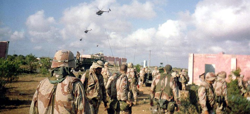 Army soldiers of Company B, 2nd Battalion, 14th Infantry Regiment, watch helicopter activity over Mogadishu, Oct. 3, 1993. Later the same day and throughout the night, the battalion's A and C Companies were part of a rescue convoy assembled for nearly 100 Rangers who had become trapped in the city after two Black Hawks were shot down.