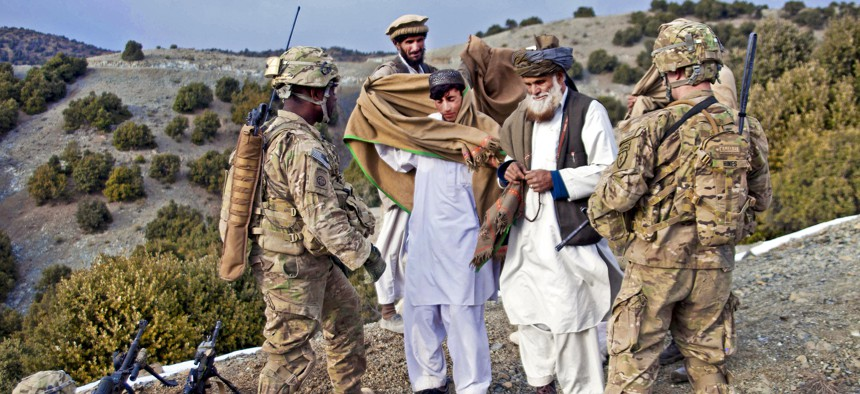 U.S. Army soldiers greet local Afghans while on a patrol near the Enzarkay Pass, March 2, 2012.