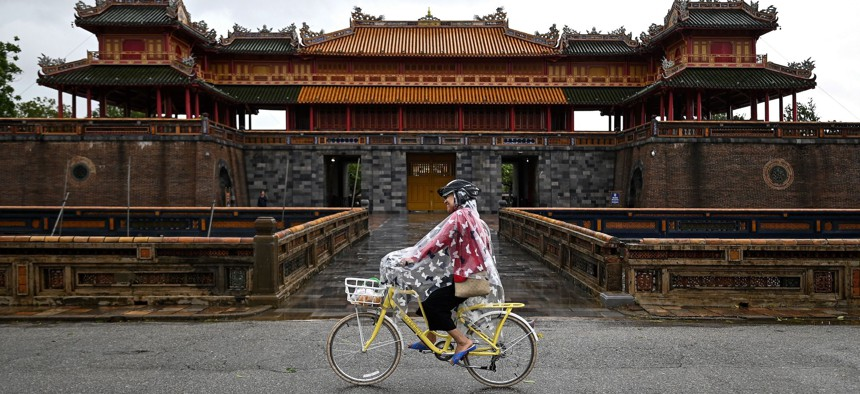 A woman covers her bicycle from the rain as she rides past the Hue Imperial Palace in central Vietnam's city of Hue on October 17, 2020.