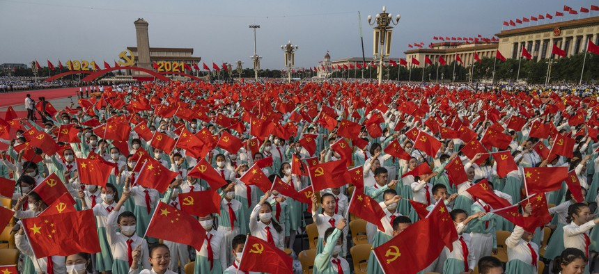 Chinese students wave party and national flags at a ceremony marking the 100th anniversary of the Communist Party at Tiananmen Square on July 1, 2021 in Beijing, China.