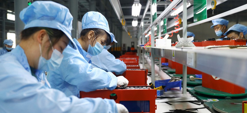 Employees assemble lithium-ion batteries at a factory in Huaibei, Anhui Province of China.