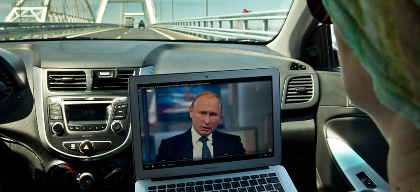 People watch a broadcast of Russian President Vladimir Putin's 2018 question-and-answer session on a laptop in a car.