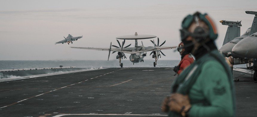 An F/A-18E Super Hornet and an E-2C Hawkeye launch from the flight deck of the aircraft carrier USS Theodore Roosevelt.