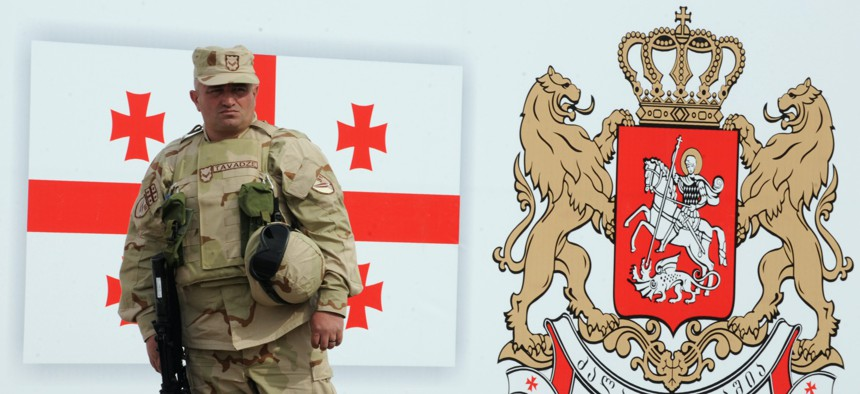 A Georgian soldier stands in front of a drawing of a Georgian flag and national emblem during a farewell ceremony before a deployment to Helmand province, Afghanistan, in 2010.