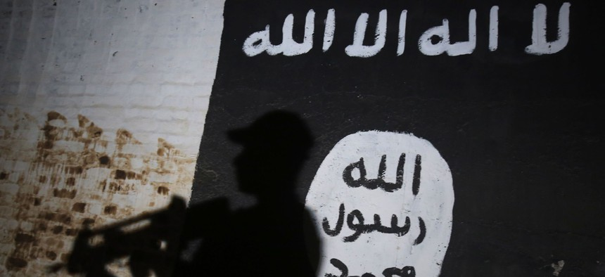 A member of the Iraqi forces walks past a mural bearing the logo of the Islamic State on March 1, 2017.
