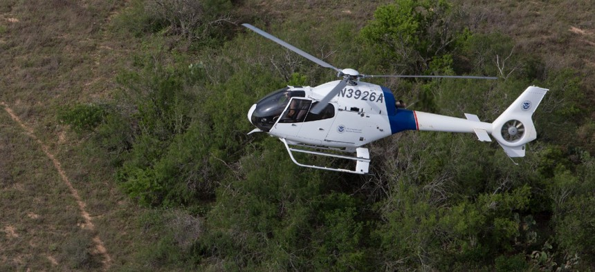 A Customs and Border Protection Air and Marine Operations agent patrols in an EC120 helicopter checking from the air for border crossers, drug smugglers and any other illegal activities along the Laredo, Texas border.